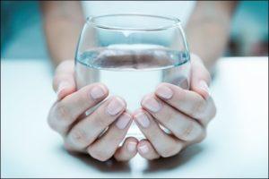 ידיים מחיזקות כוס מים
